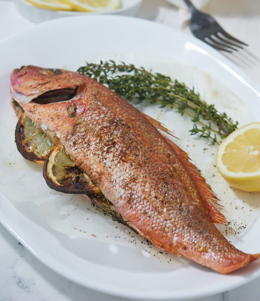 Air fryer whole fish served on a white plate.