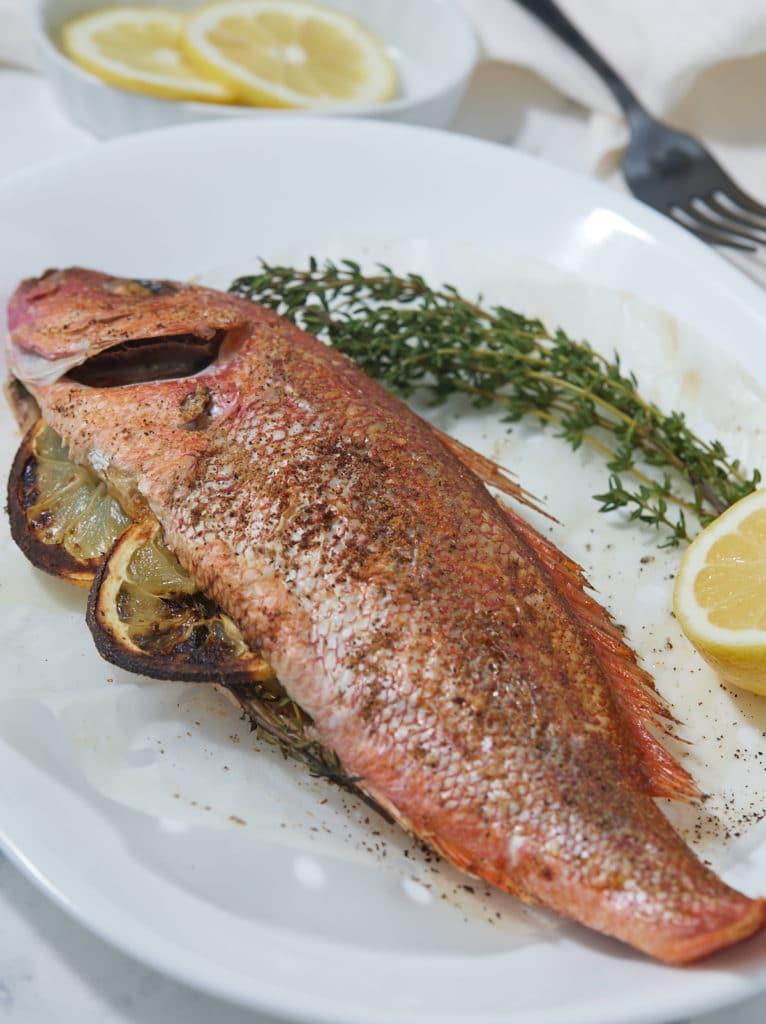 Whole fish served on a plate with thyme and fresh lemons.