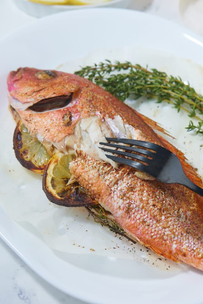 A fork flaking away the skin of the fish to reveal the flesh.