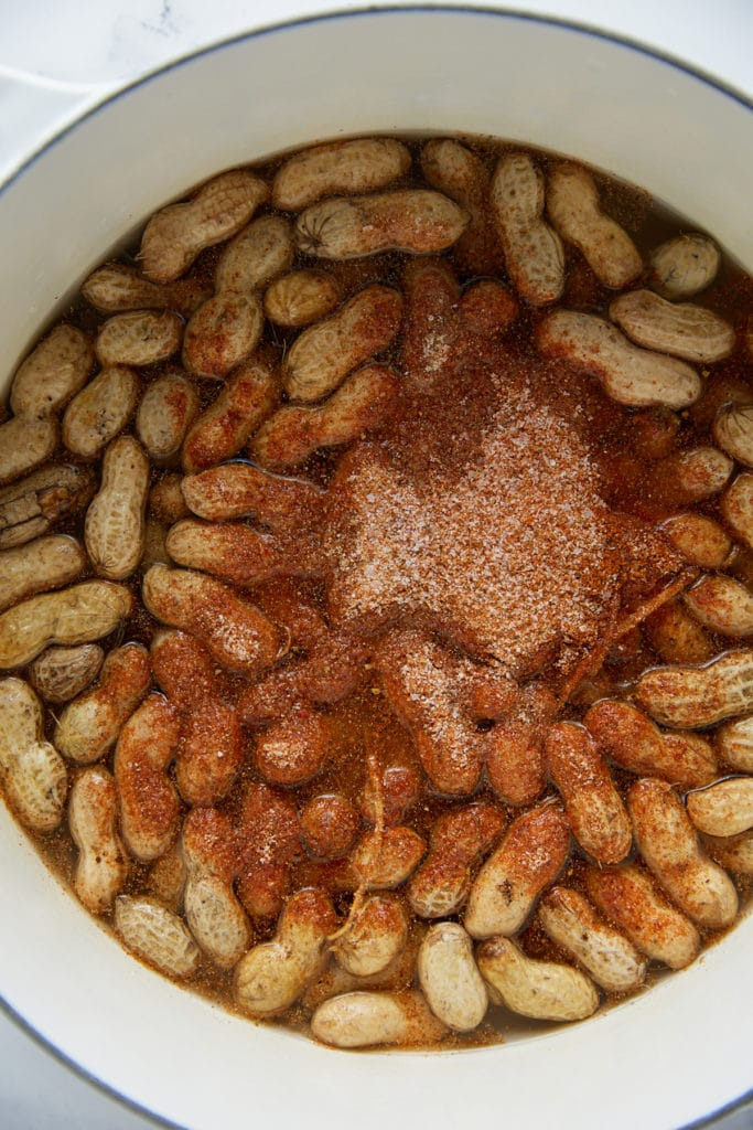 Seasonings added to the peanuts in a large pot.