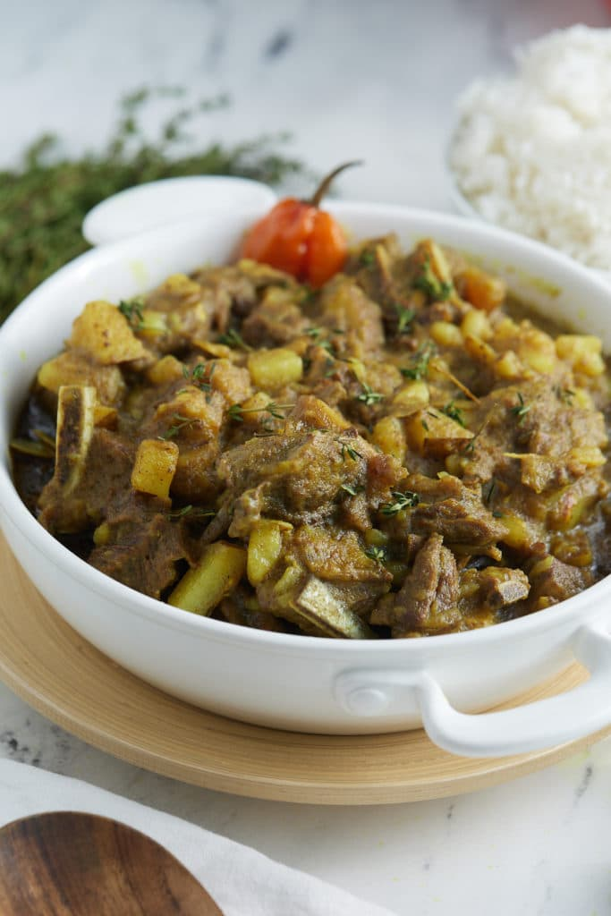 Jamaican curry goat in white bowl