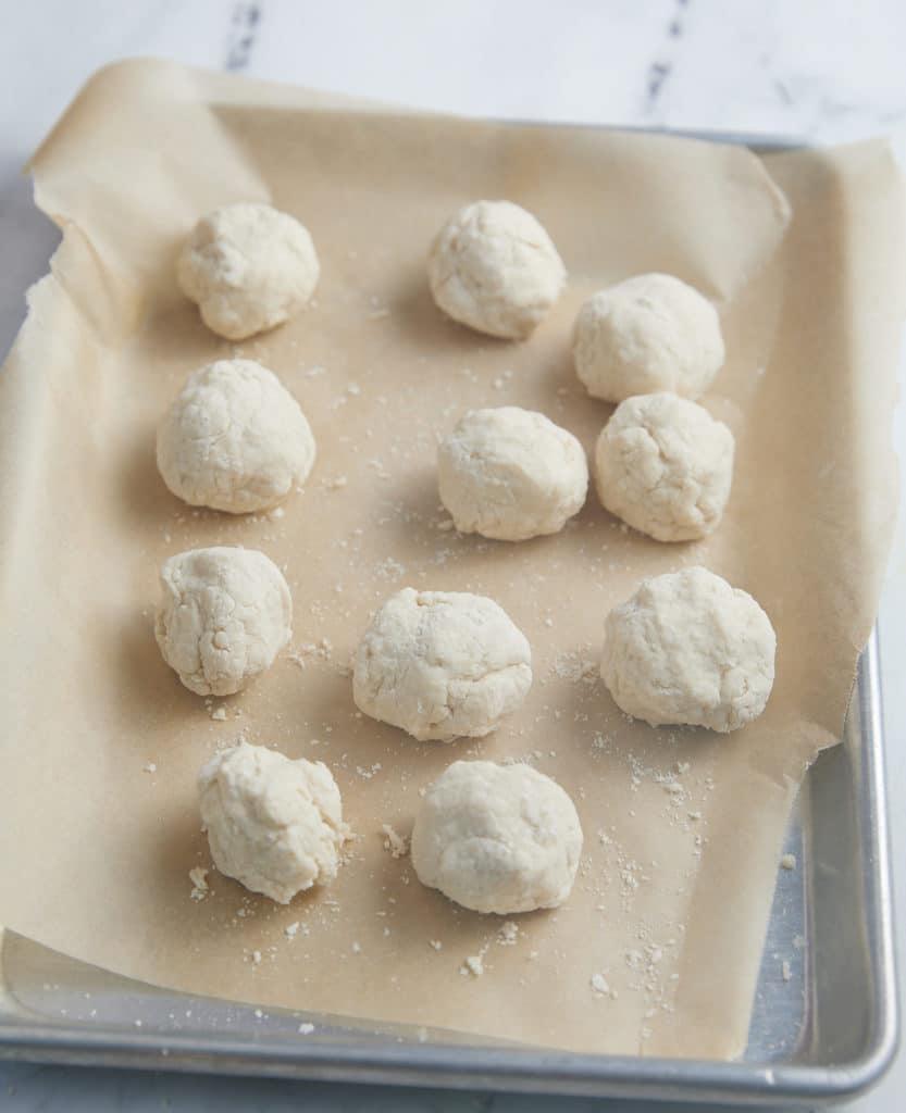 dumplings on parchment lined baking sheet