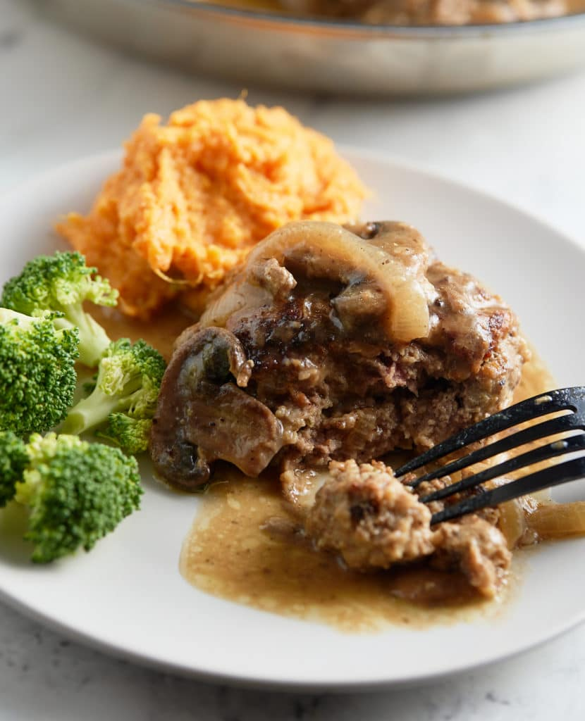 A salisbury steak topped with mushroom gravy on a white plate.