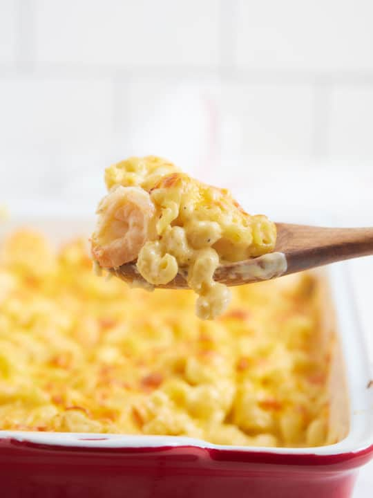 Mac and cheese on a wooden spoon.
