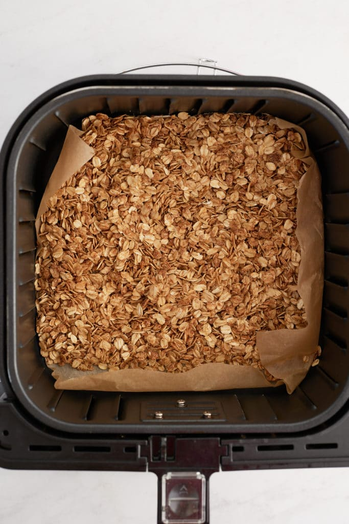 The cooked granola in an air fryer basket.