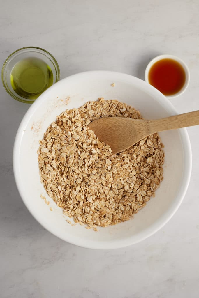 The dry granola ingredients in a bowl with a spoon.