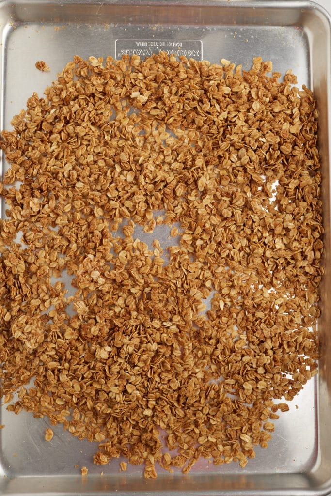 Granola spread out on a baking sheet to cool.