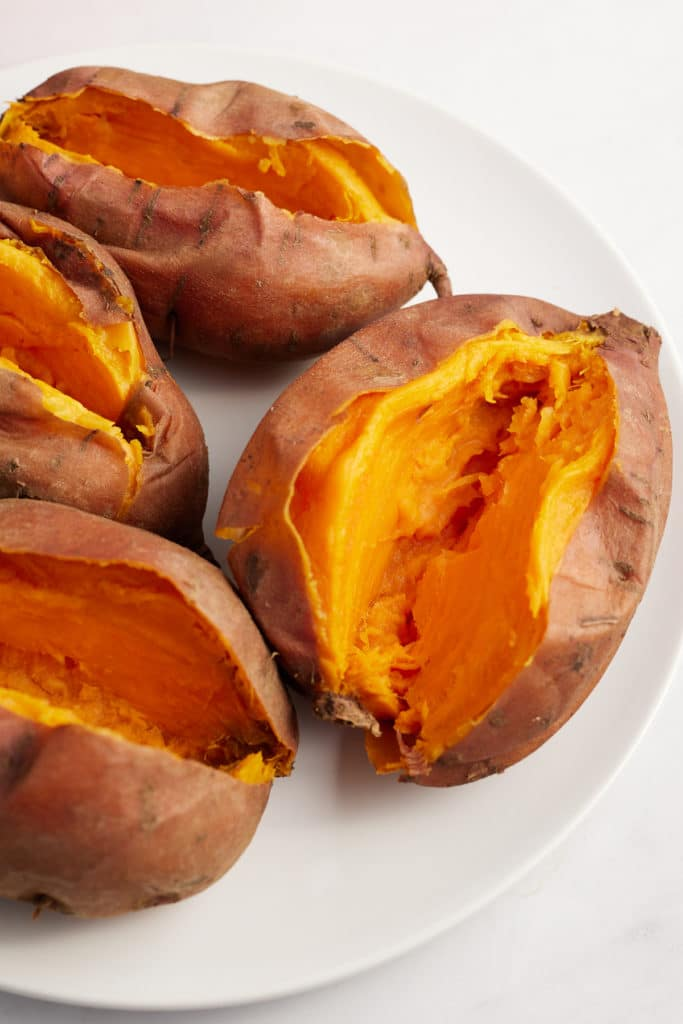 Four sweet potatoes on a white plate cut in half.