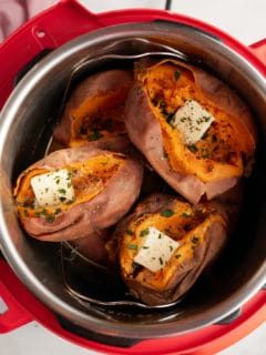 Cooked sweet potatoes in an Instant Pot, split open and topped with butter and fresh herbs.