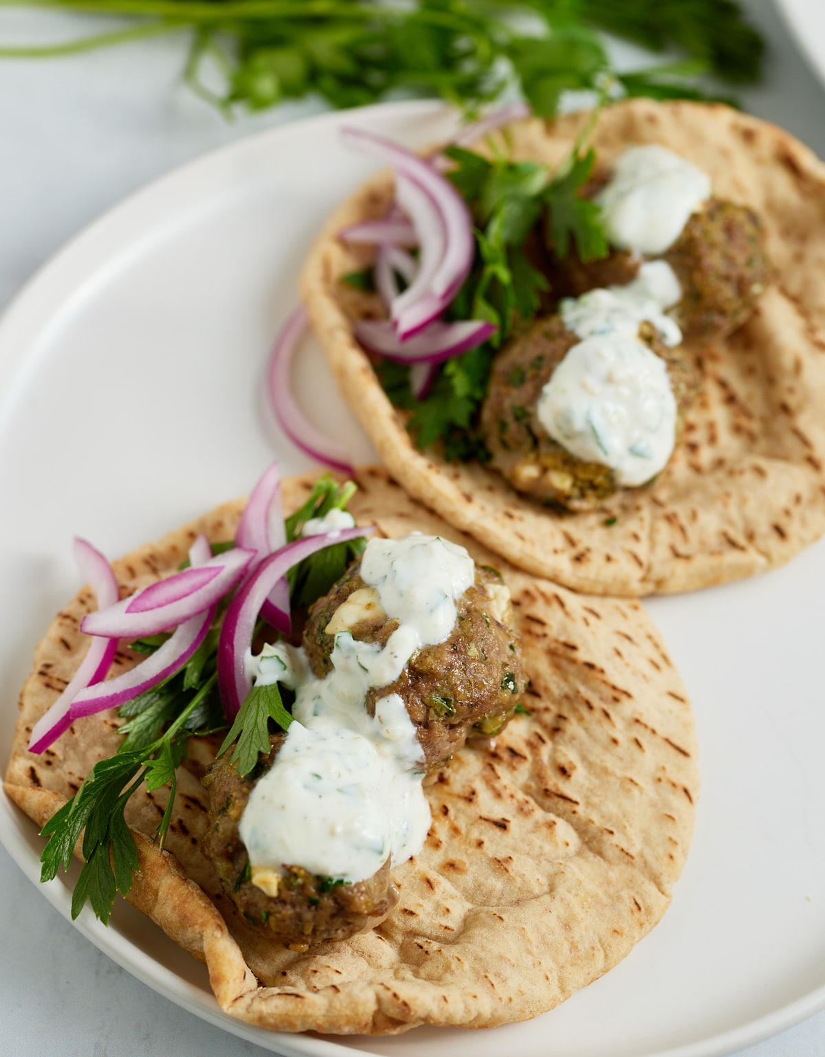 close up of lamb meatballs on pita bread and toppings