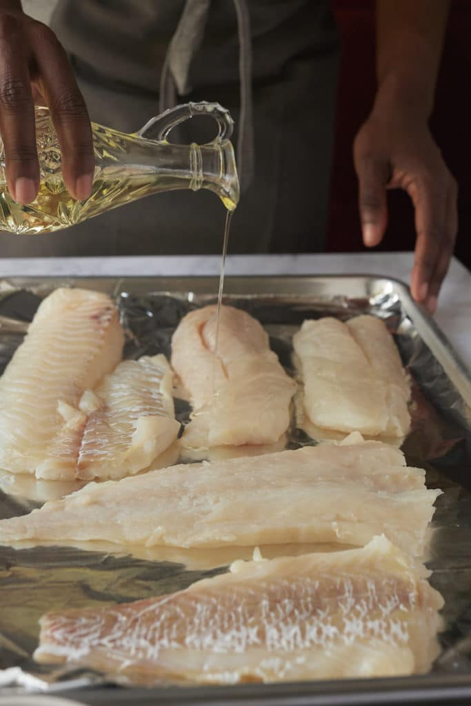 Drizzling oil over fish fillets.