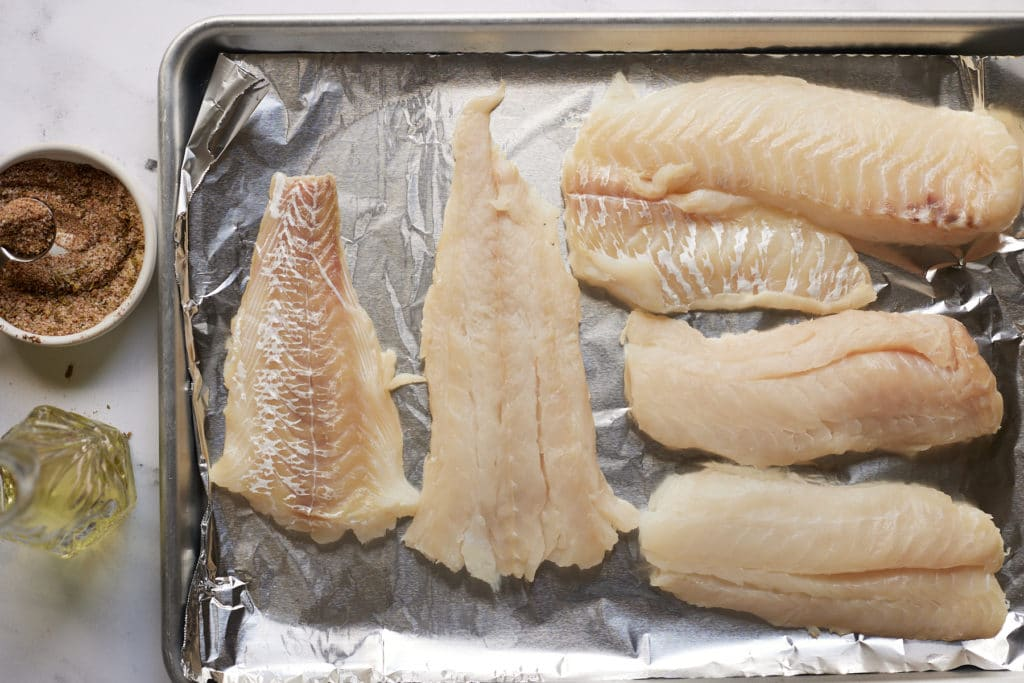 Fish fillets on a lined baking tray next to seasoning and oil.