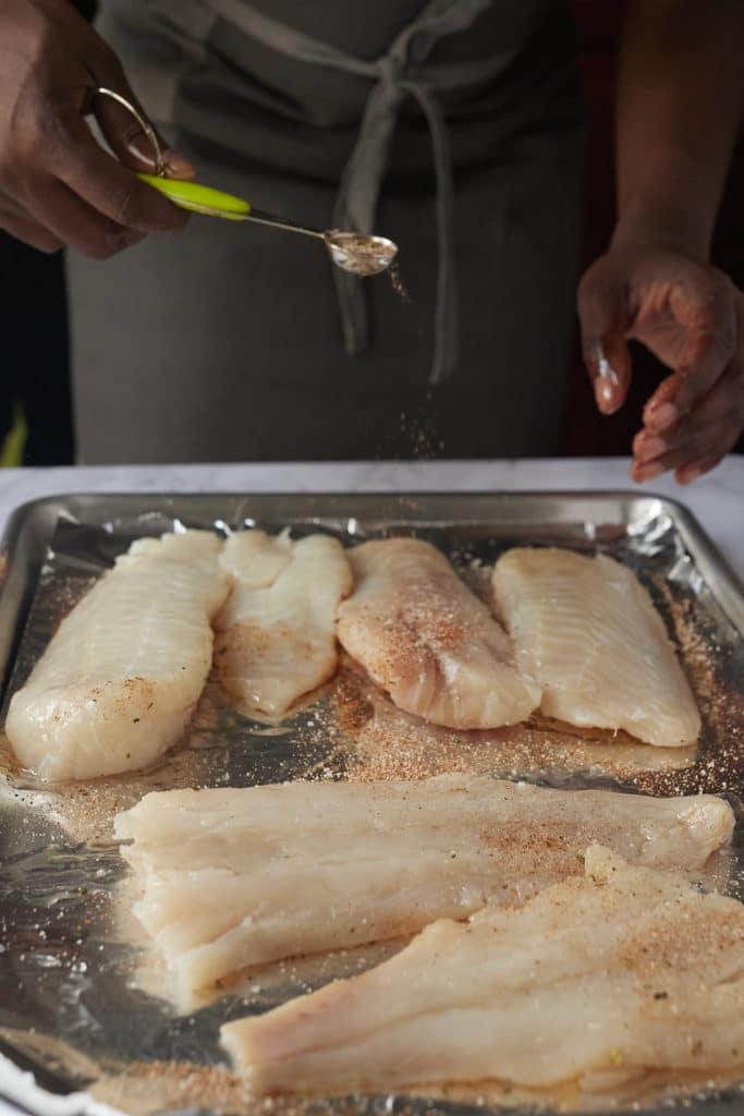 Sprinkling seasoning of fish fillets.