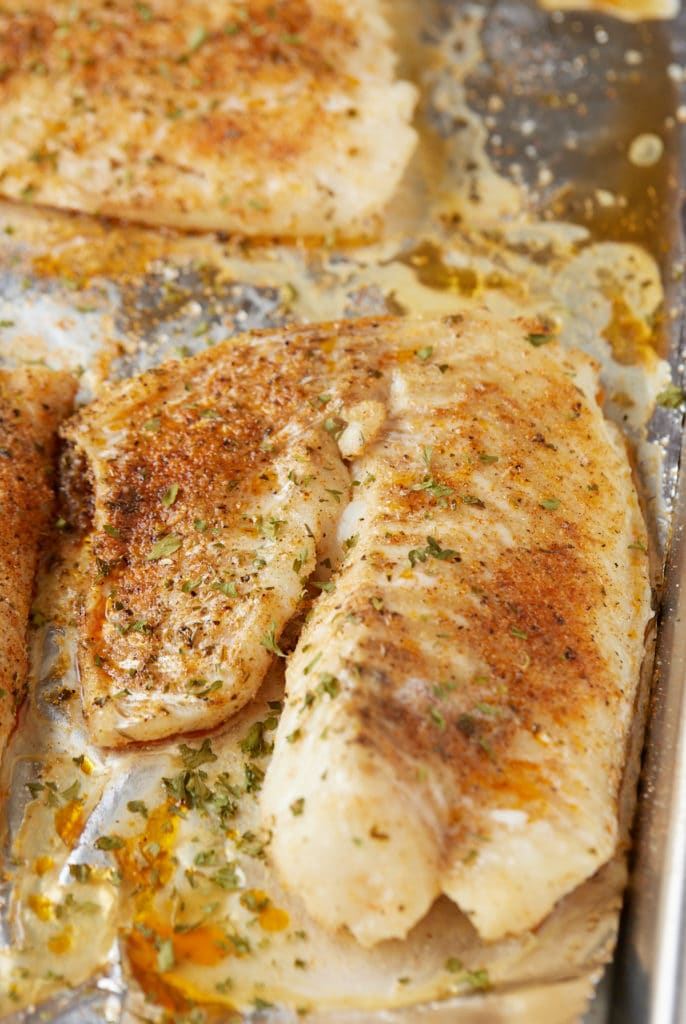 Two baked fish fillets on a baking sheet ready to serve.