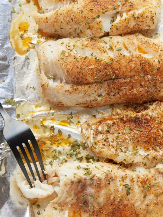 Baked fish fillets on a baking sheet with a fork.