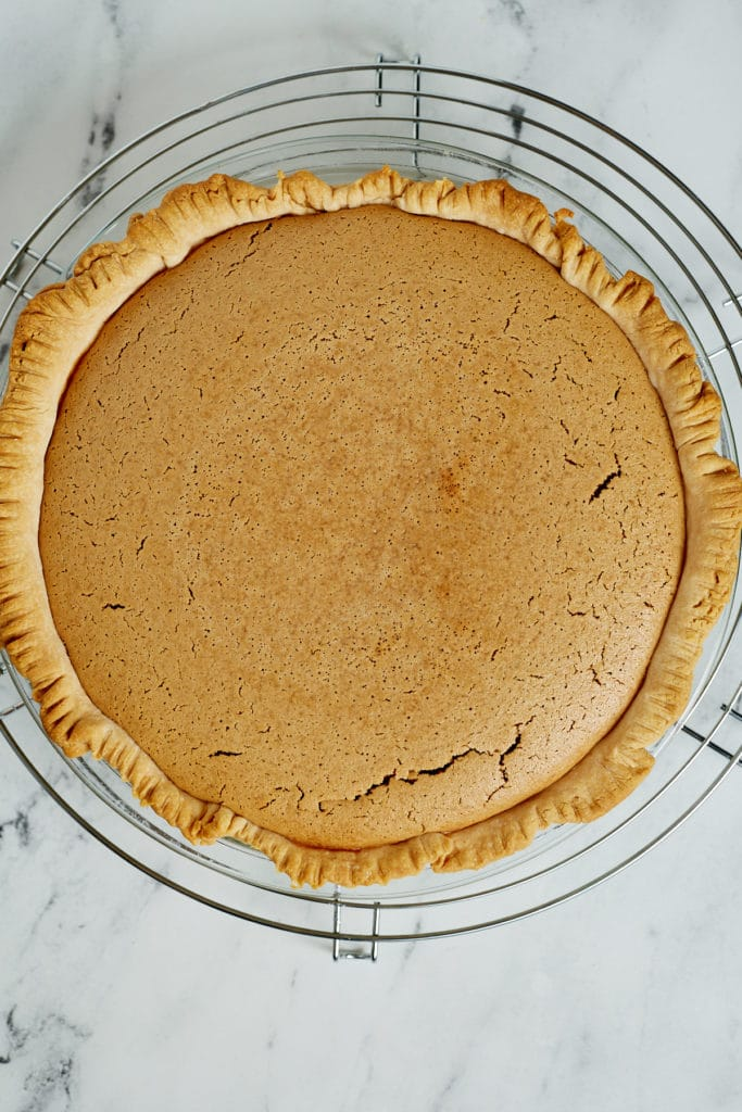 A baked pinto bean pie on a cooling rack.