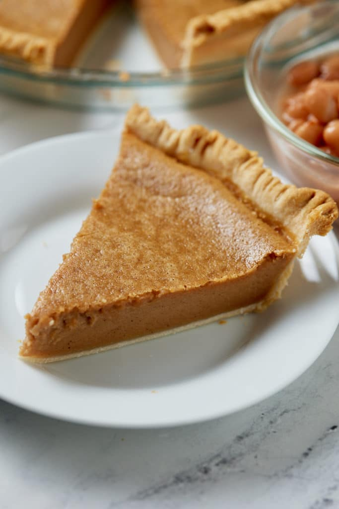 A slice of pinto bean pie served on a white plate.