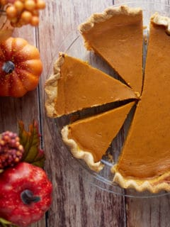 A homemade pumpkin pie cut into slices on a wooden table.