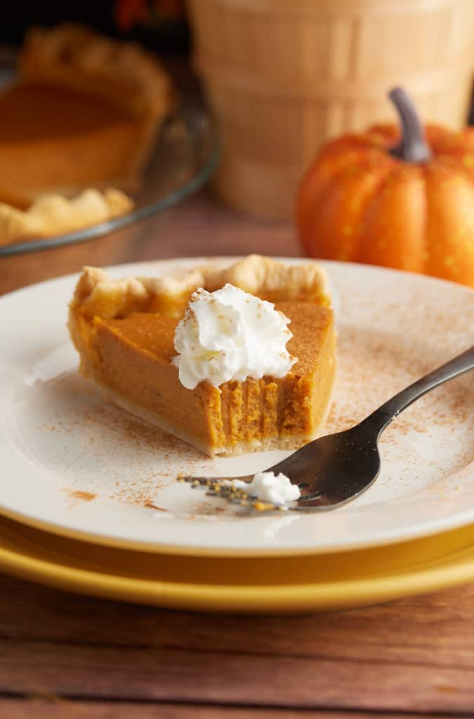 A slice of pupkin pie on a plate with a fork.