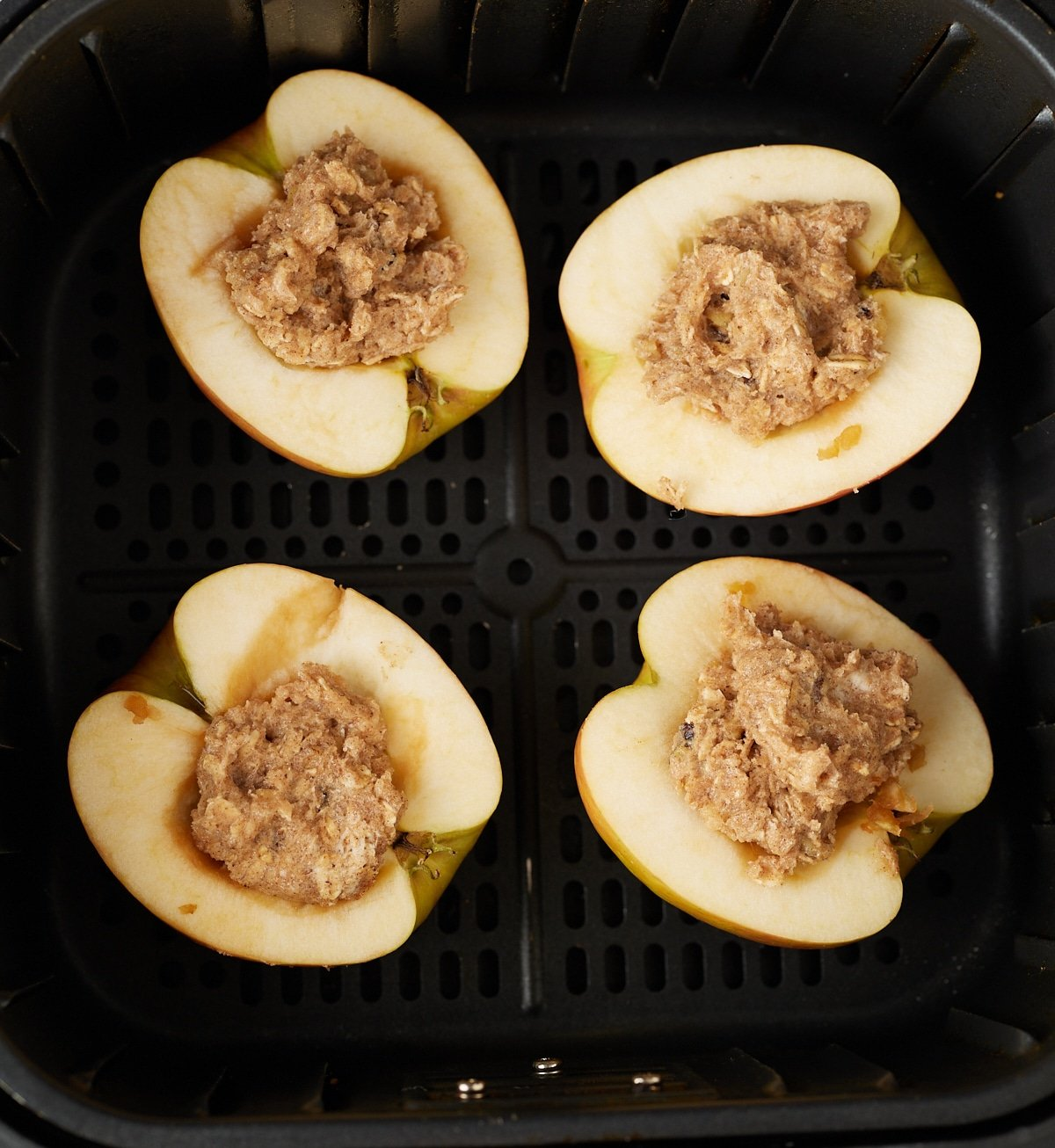 The apples with filling placed into the air fryer basket.