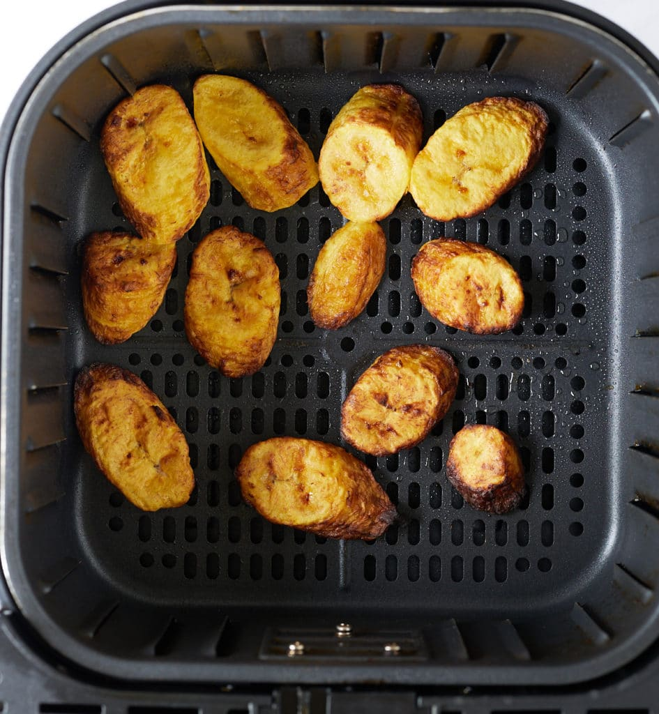 The plantains in the air fryer basket after being cooked.