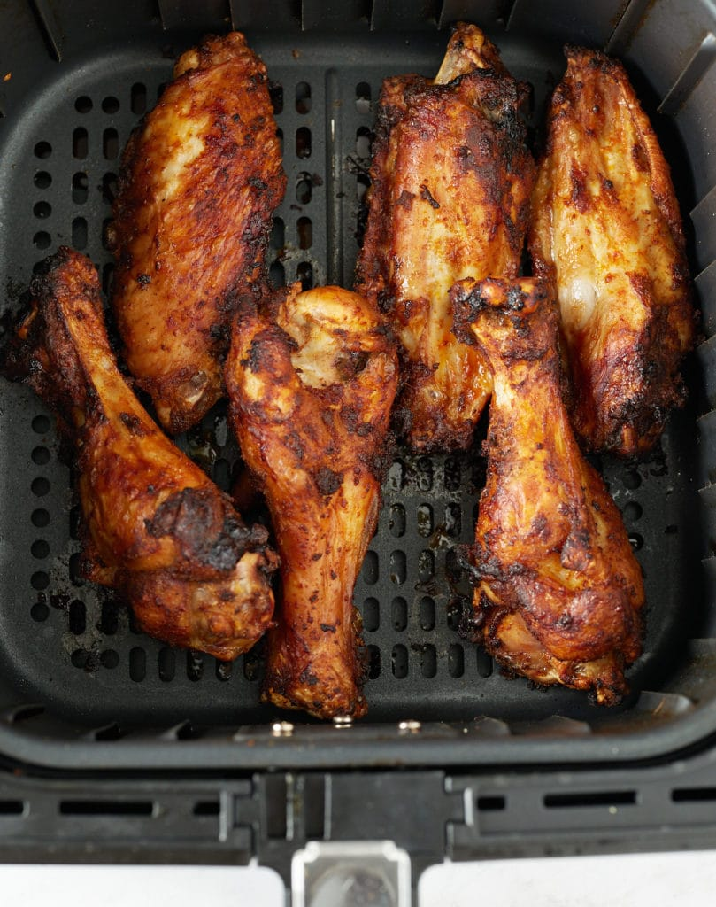 The wings in the air fryer basket after being cooked.