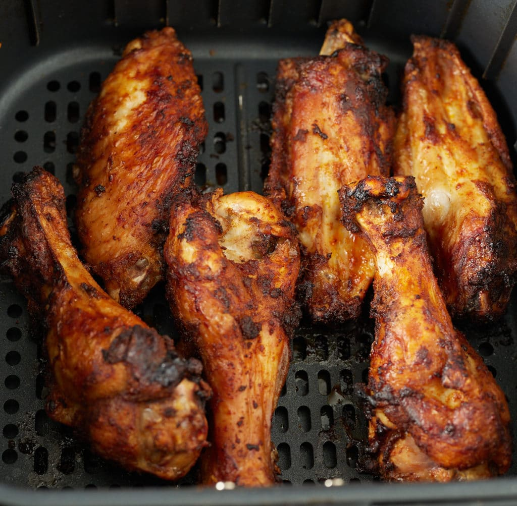 Six cooked turkey wings in an air fryer basket.