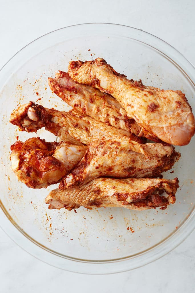 Turkey wings in a bowl rubbed with the seasonings.