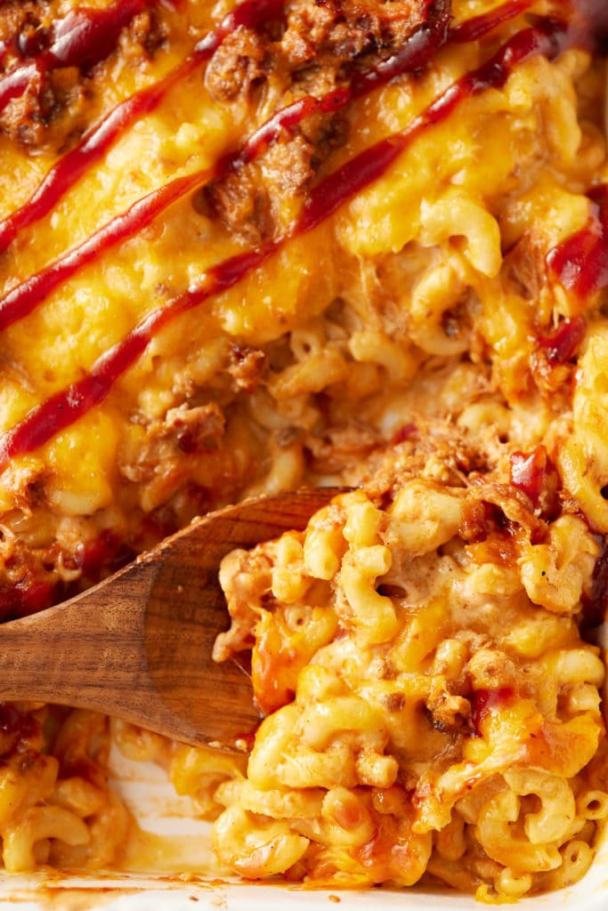 A wooden spoon serving the BBQ mac and cheese.