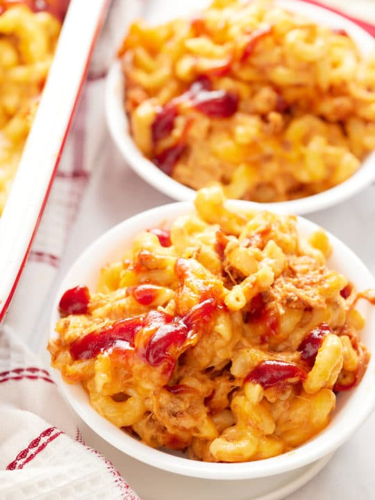 Two bowls of mac and cheese topped with BBQ sauce.