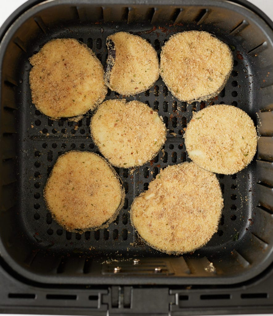 The breaded eggplant slices in the air fryer basket.
