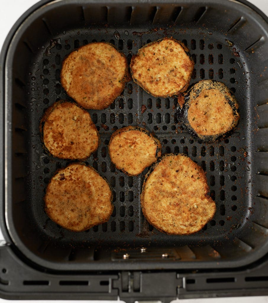 The cooked eggplant slices in the air fryer basket.