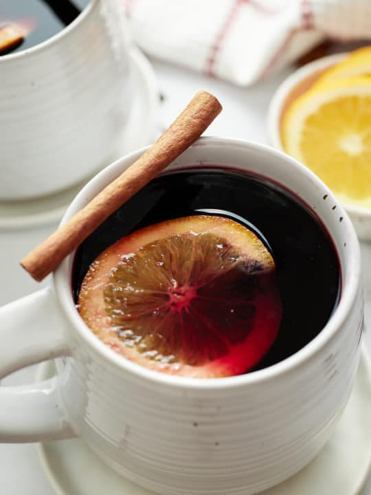 Mulled wine served in a mug with a cinnamon stick and orange slice.