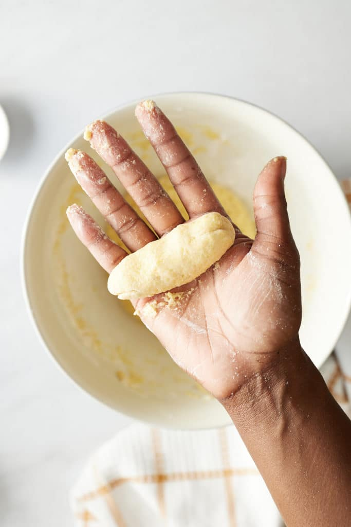 festival dough rolled into long oval shape in hand