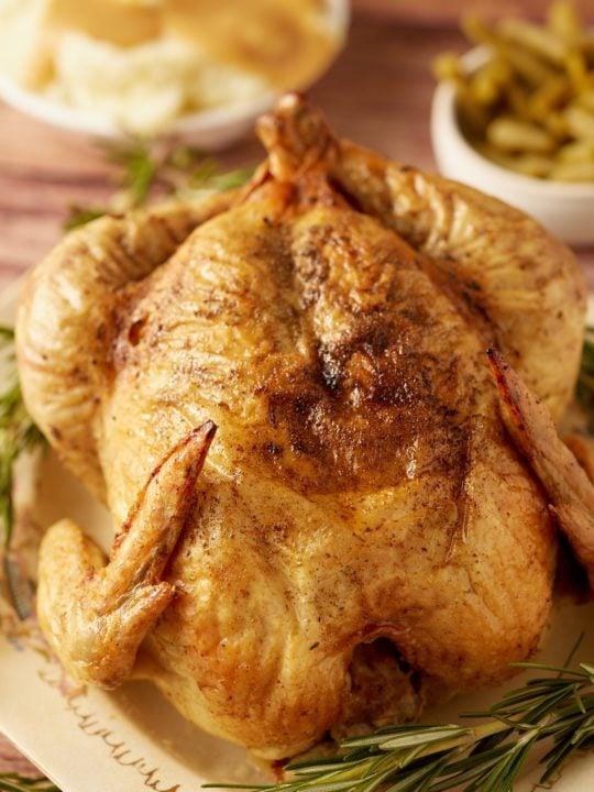 A Thanksgiving chicken served next to fresh herbs.