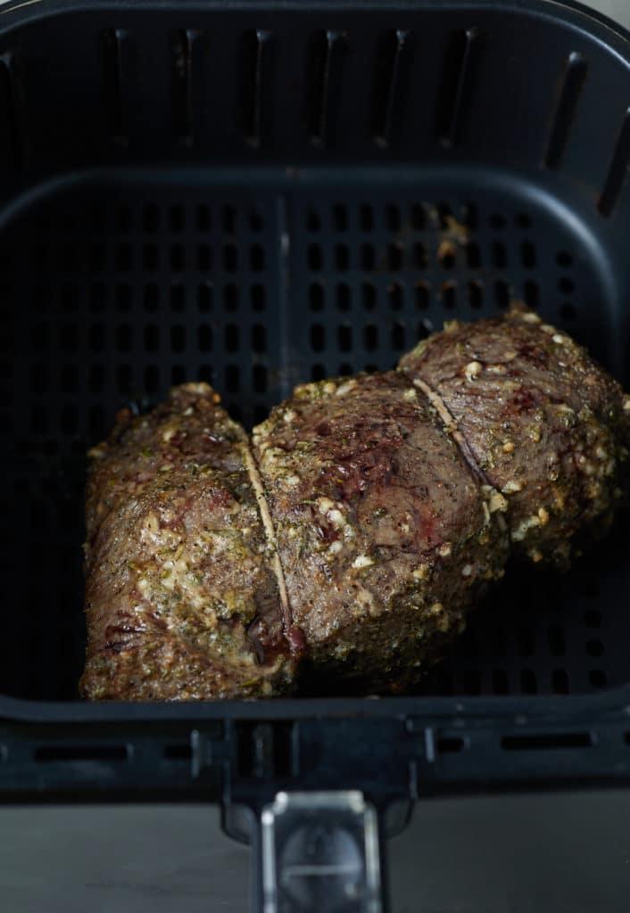 The cooked beef tenderloin in the air fryer basket.