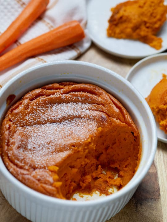 Carrot souffle in a white dish served on to two plates.