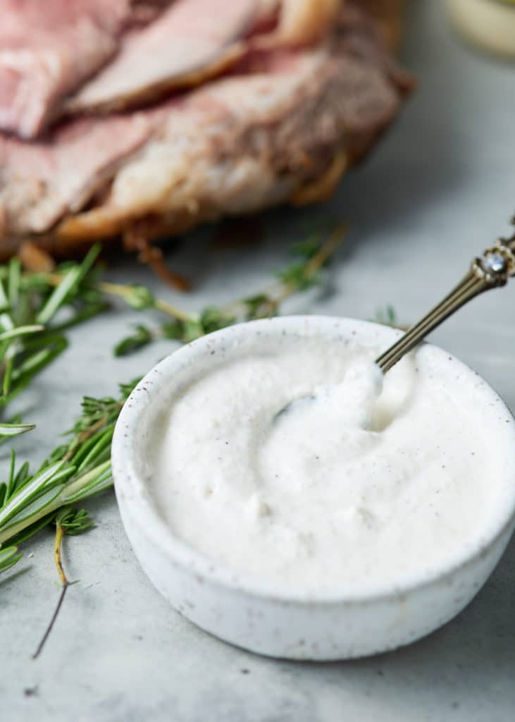 Close up of horseradish sauce in a bowl net to fresh herbs.