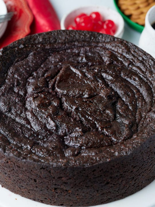 jamaican black cake on table with cherries and drink behind it