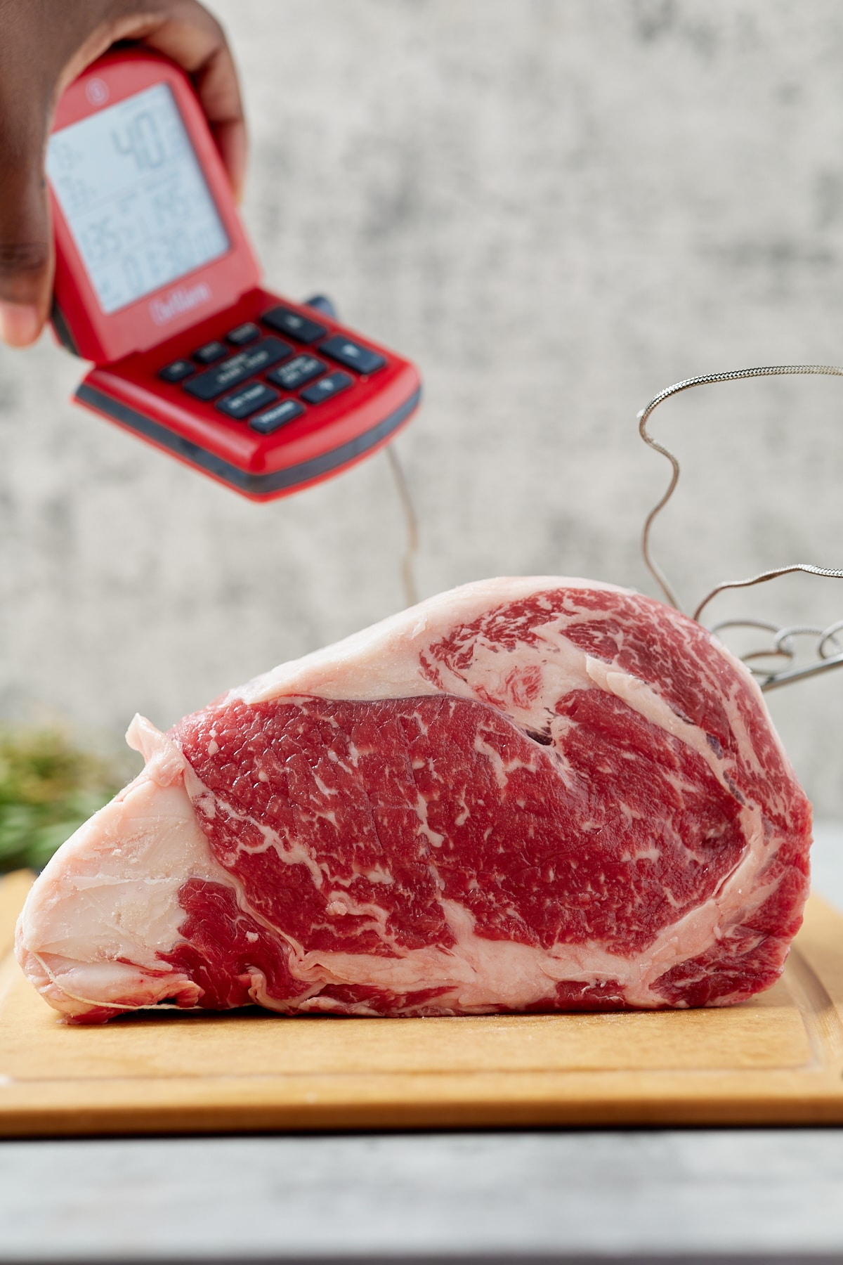 A raw boneless cut of beef with an instant read thermometer.